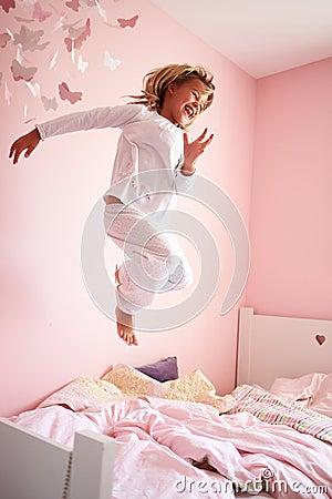Junges Mädchen, das auf ihr Bett springt