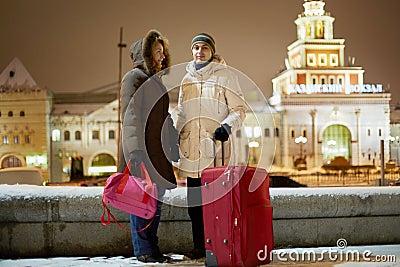 Junges Paar mit großem rotem Rollkoffer steht am Abend