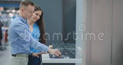 Junges Paar w?hlt cooktop im Speicher von Haushaltsger?ten stock footage