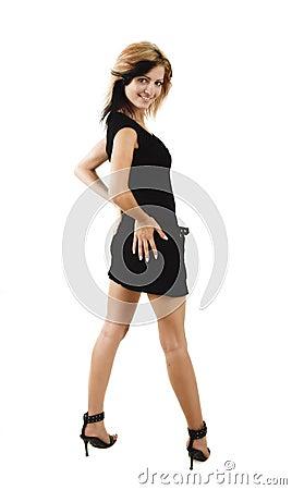 Junges Schönheitsmädchenportrait, das in einem netten schwarzen Kleid aufwirft