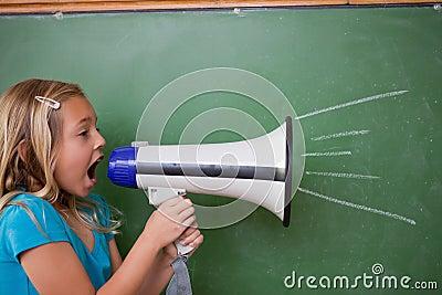 Junges Schulmädchen, das durch ein Megaphon schreit