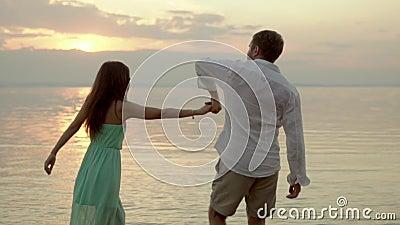 Junges Tanzen des glücklichen Paars auf dem Strand auf dem Sonnenuntergang Konzept der Liebe stock video footage