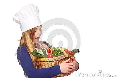 Junior cook holding a basket with vegetables