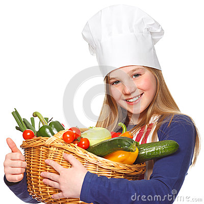 Junior cook holding a basket with vegetables