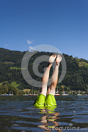 Just the legs of a teenager are over the water sur