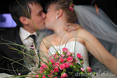 Just married couple kissing in limousine