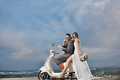Just married couple ride white scooter