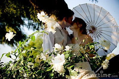 Just married couple standing and kissing in white