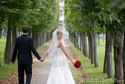 just married couple walking down the parkway stock
