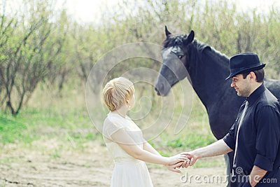 Just wedded young couple with horse dressed retro