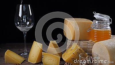 KÄSE UND WEIN Vielzahl des Käses gesetzt auf hölzernen Hintergrund Wein wird in Weinglas in der Zeitlupe gegossen stock video