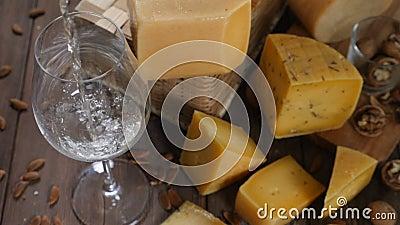 KÄSE UND WEIN Vielzahl des Käses gesetzt auf hölzernen Hintergrund Wein wird in Weinglas in der Zeitlupe gegossen stock footage