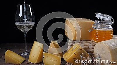 KÄSE UND WEIN Vielzahl des Käses gesetzt auf hölzernen Hintergrund Wein wird in Weinglas in der Zeitlupe gegossen stock video footage