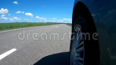 Körning av en bil på en huvudväg längs gröna gräs- fält i en solig sommardag Kameran monterade på en sida av bilen arkivfilmer