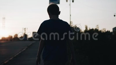 Kühle Gesamtlänge des Jungen bei Sonnenuntergang Der Junge geht entlang die Ufergegend Die Kamera folgt ihm stock footage