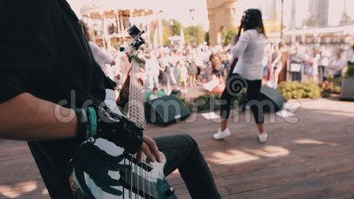 Kühler Bass-Spieler führt am Stadium mit seinem Band durch Er ist sehr kühl und spielt mit Ihren Fingern auf den Schnüren stock video footage