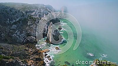 4K Ανθεκτικοί βράχοι στην ακτογραμμή του ατλαντικού σε πρωινή ομίχλη με τον φάρο Cabo da Roca στο παρασκήνιο στη Sintra, Πορτογαλ απόθεμα βίντεο