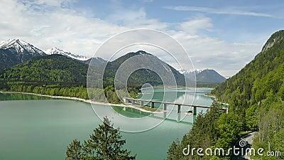 4K καταπληκτική γέφυρα κηφήνων πέρα από τη λίμνη Sylvenstein, ανώτερη Βαυαρία συσσώρευσης ( Γερμανία Μαΐου, φιλμ μικρού μήκους