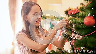 4k πλάνα από ένα όμορφο χαμογελαστό κορίτσι να κρέμεται από ένα πολύχρωμο μπιχλιμπίδι στο χριστουγεννιάτικο δέντρο στο σπίτι Οικο φιλμ μικρού μήκους