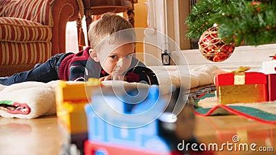 4k видео, на котором мальчик лежит на полу под рождественской елкой и смотрит на игрушечный поезд, катающийся на железной дороге  сток-видео