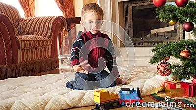 4k кадры маленького малыша, который смотрит на игрушечный поезд, катающийся на круговой железной дороге в гостиной Дети, получающ акции видеоматериалы
