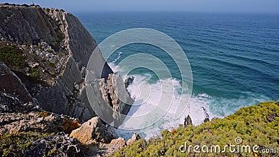 4K Aussicht auf die schroffen Felsen am Strand von Praia Grande, Portugal Atlantische Wellen des weißen Ozeans, die auf die Felsk stock video
