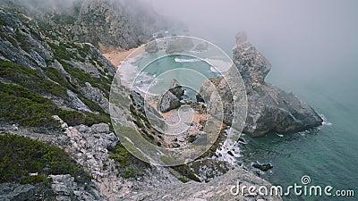 4K-Aussicht von oben von Felsen in Nebel am Strand von Praia da Ursa in Sintra, Portugal stock video