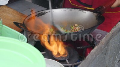 4K Close up of Thai street food vendor cooking a hot chilli chicken pork stir fry in large wok. these vendors are found. Pattaya, Thailand - February 1, 2020: 4K stock video footage