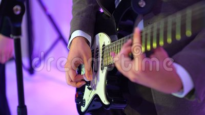 4k guitarist plays acoustic guitar on night club stage, flashes of colour lights. Guitarist plays acoustic guitar on night club stage against flashes of