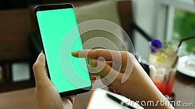 4k lengte sluit omhoog de holdingssmartphone van de vrouwenhand met het groene scherm bij koffiewinkel, gebruikend vingeraanrakin stock footage