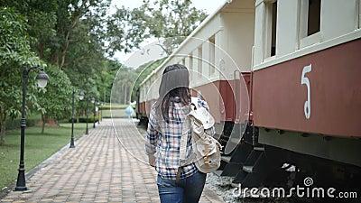 4k lengte twee scènes van gelukkige Aziatische toeristenvrouw bij station, gang aan de trein en voeren op trede op reis in Azië l stock videobeelden