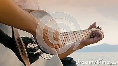 4 K próximo de um homem tocando violão acústico na praia durante o pôr do sol, sentindo relaxamento vídeos de arquivo