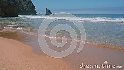 4 K Praia da Adraga strand Vita atlantiska havsvågor som rullar mot sandstrand Sintra, Portugal arkivfilmer