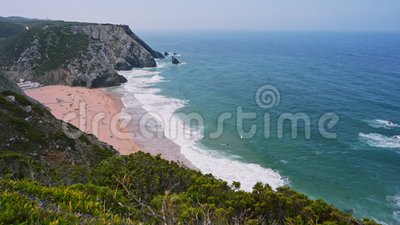 4K Praia da Adraga surf strand Vita atlantiska havsvågor som rullar mot sandstrand med turister Sintra, Portugal stock video