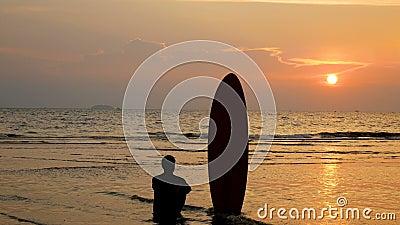 4K silhouette d'homme de surfer se reposant sur la plage de mer avec de longs panneaux de ressac au coucher du soleil sur la plag banque de vidéos