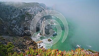 4K Tålig kustlinje vid Atlanten med dimma, bladverk och Cabo da Roca fyr i bakgrunden i Sintra stock video
