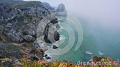 4K Tålig kustlinje vid Atlanten med dimma, bladverk och Cabo da Roca fyr i bakgrunden i Sintra lager videofilmer