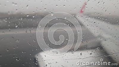 4k video dei flussi d'acqua piovana che fluiscono sulla finestra del velivolo durante il decollo da una pista bagnata durante una stock footage