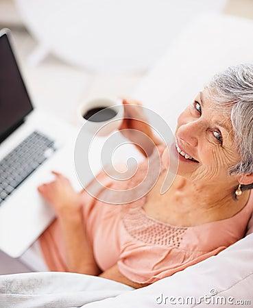Kaffe som dricker den gammala användande kvinnan för lycklig bärbar dator