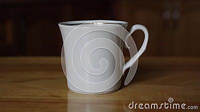 Kaffeetasse aus weißem Porzellan auf braunem Holztisch stock video