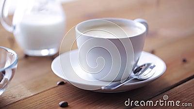 Kaffeetasse und Bohnen, die zum Holztisch gießen stock video footage