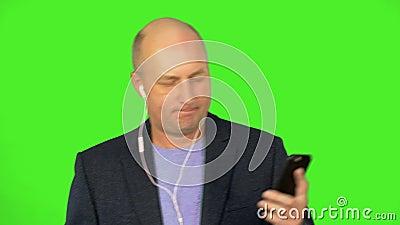 Kahler erwachsener kaukasischer Mann hören Musik am intelligenten Telefon über Kopfhörer und Tanz Tanzenmann in der blauen Klage  stock video