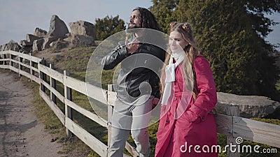 Kamera nähert sich zwei Personen an einem Holzzaun im Herbstpark stehen und reden Relaxter Hippie Nahost-Mann und stock video footage