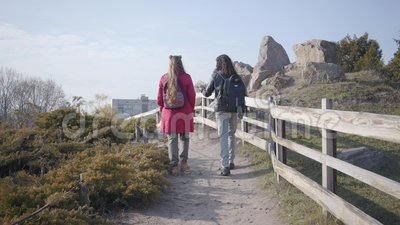 Kamera nach Mann und Frau aus Mittelost und Kaukasian, die über Holzzaun im Freien spazieren Positives Hippie-Paar stock video footage