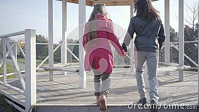 Kamera nach Mann und Frau, die im Herbstpark in den Pavillon geht Junge multirassische Paare im Freien Blond stock video footage