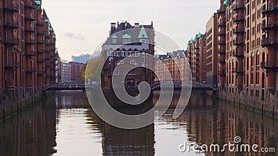 Kanaal in het oude magazijndistrict Speicherstadt in Hamburg, Duitsland Rode stenen historische gebouwen stock footage