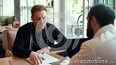 Kandidaat voor een baan stelt zich voor aan de werkgever in een ontspannen café stock video