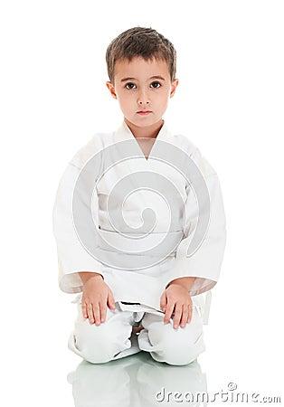 Karate boy sitting in white kimono