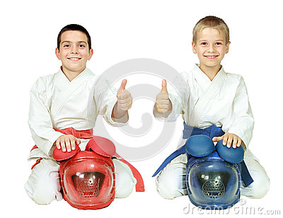 Karate children sit in a ritual pose with helmets and point the finger isolated
