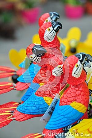 Kaufen Sie mich! - dekorativer Papagei, der heraus in einer Reihe steht